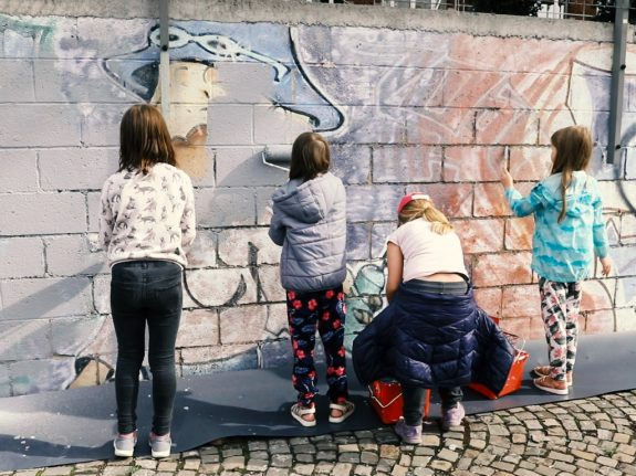 Kinderen schilderen een oude muur wit.